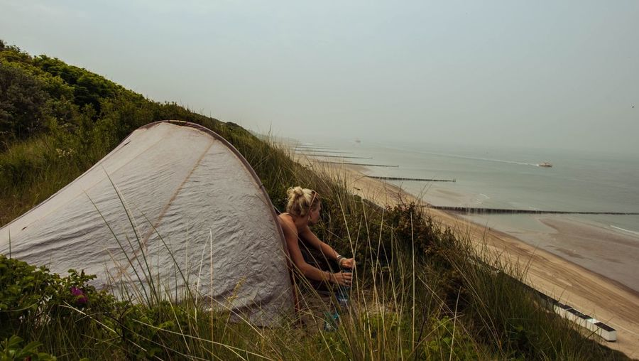 Woman in tent on mountain against beach