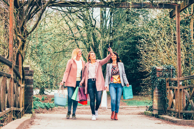 three young women in a park smiling and caring shopping bags they take a selfie while on walking - togetherness, free time, friendship and consumption concept Selfie Weekend Young Women People Friends Shopping Phone Bags Togetherness Fashion Outdoors Bestoftheday Fun Laughing Best Friends Beautiful Smile Care Carefree Activity Leisure Activity Park City Town Outside Day Casual Clothing Females Three Friendship Together Cheerful Photo Smartphone Shopper Walking Bonding Toothy Smile Emotion Positive Emotion Consumption  Free Modern Tree Full Length Plant Real People Adult Young Adult Young Women Standing Lifestyles Front View Group Of People Nature Arm Around Couple - Relationship