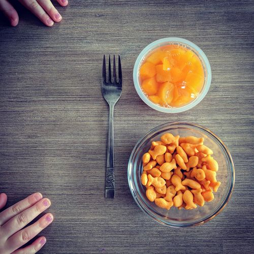 Close-up of hand holding bowl of food on table