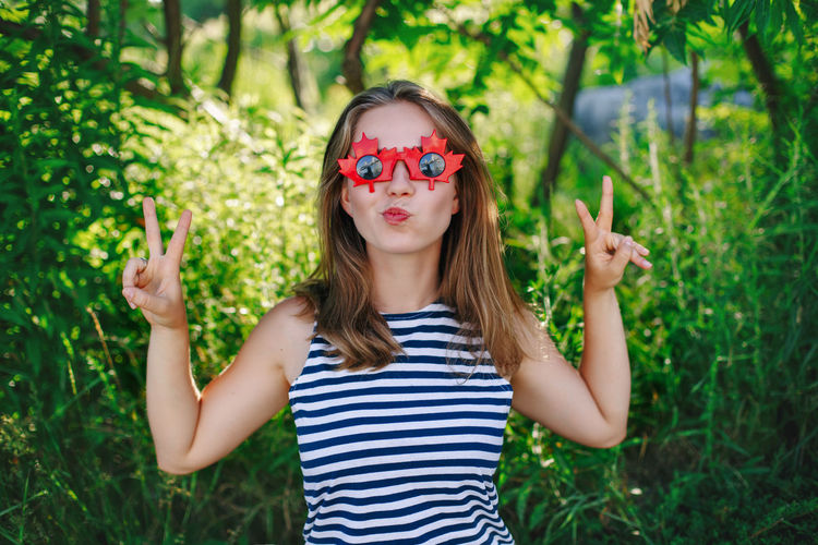 Portrait of young woman wearing sunglasses standing against plants