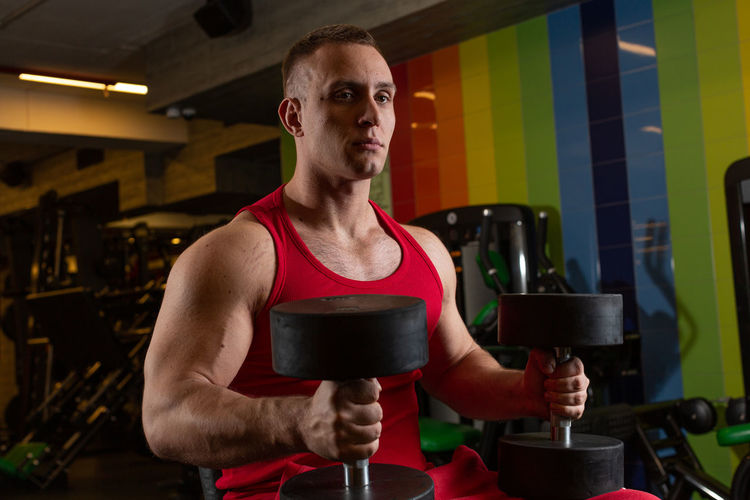 Young man holding dumbbells sitting at gym