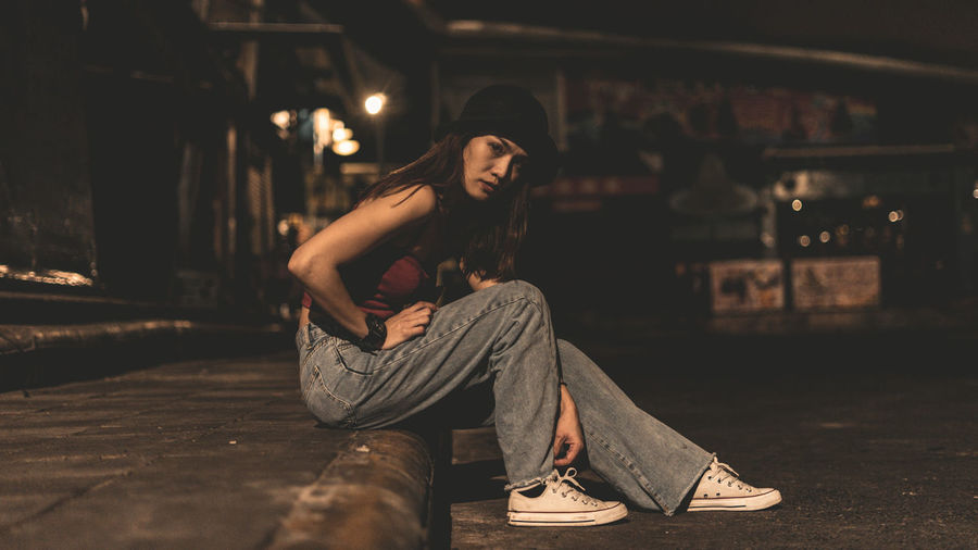 Young woman sitting in hat at night