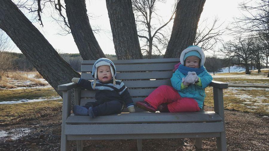 Portrait of children sitting on bench at park