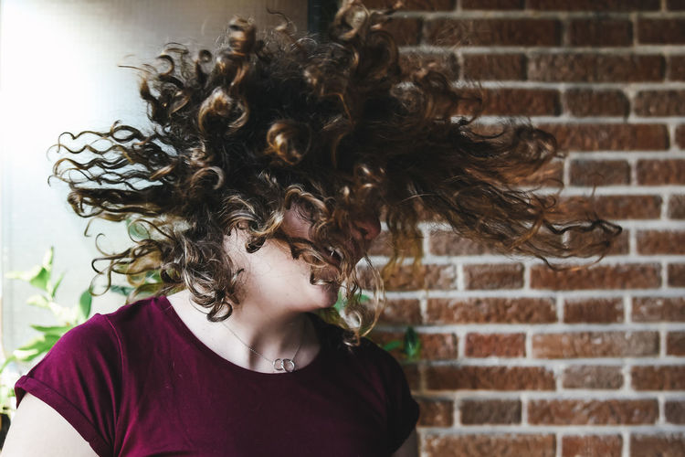 Happy Young Woman Tossing Hair Against Wall