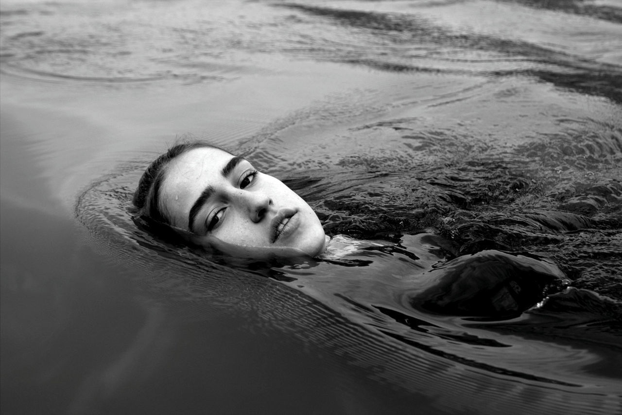 PORTRAIT OF YOUNG WOMAN RELAXING IN SWIMMING POOL