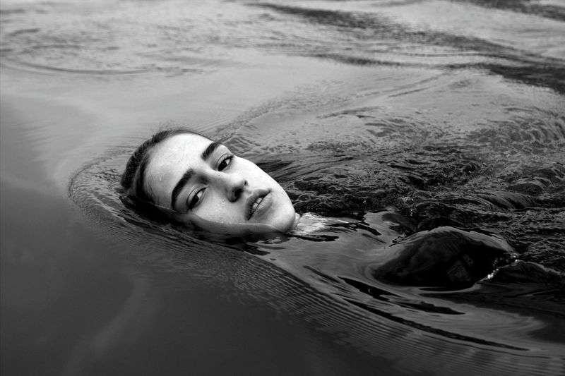Portrait of young woman lying in swimming pool