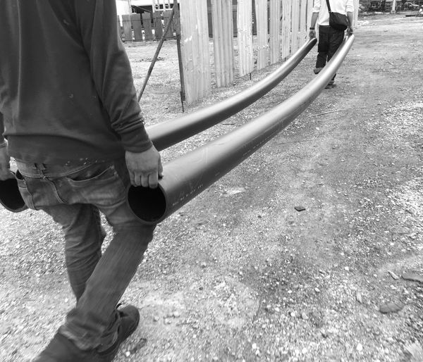 PE Pipe Real People One Person Day Outdoors Low Section Men Human Hand Construction Site Piping Work Mechanical Work Labor