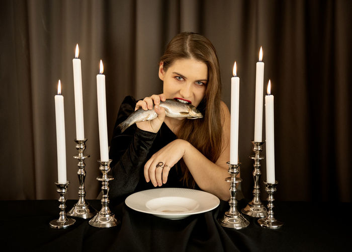 Portrait of woman eating fish
