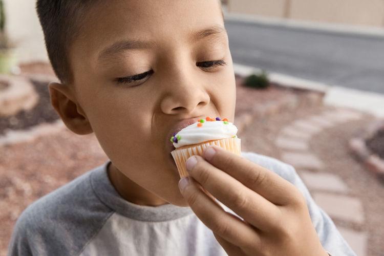 Close-up of boy eating cupcake