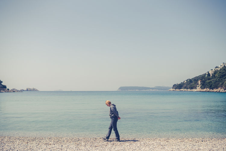 Side view of woman walking on beach against sky