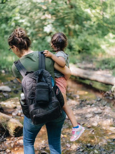 Rear view of mother and daughter walking in forest