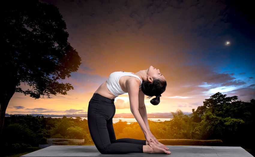 Woman Doing Yoga Against Sky During Sunset