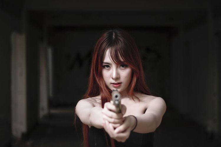 Portrait of young woman shooting with handgun in darkroom