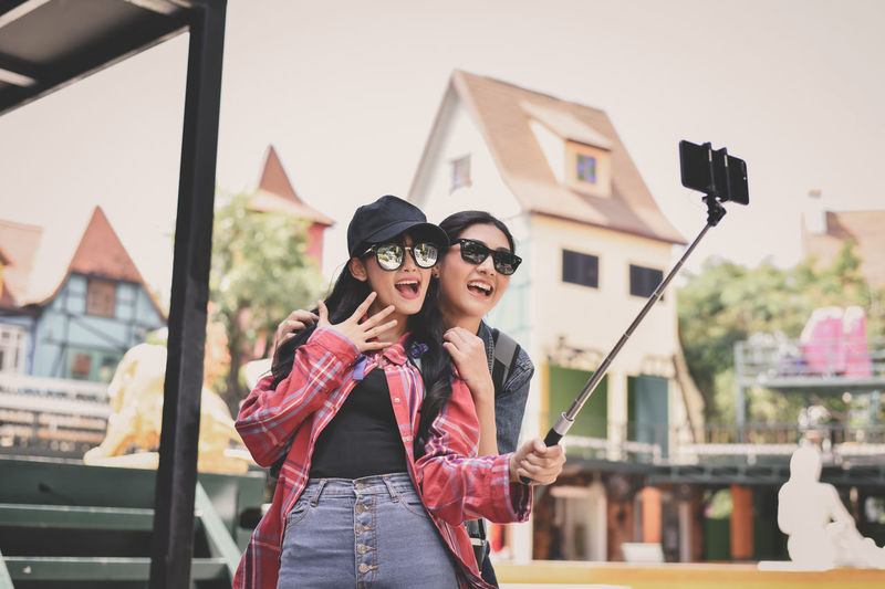 Cheerful Friends Taking Selfie With Smart Phone In City