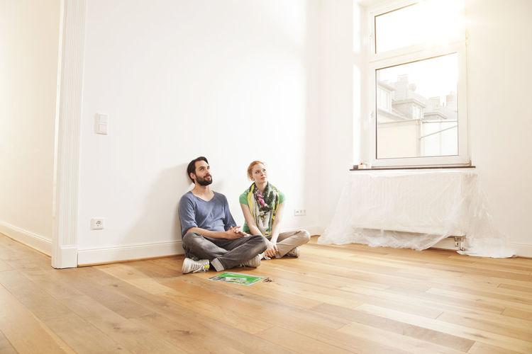 Young couple sitting on hardwood floor