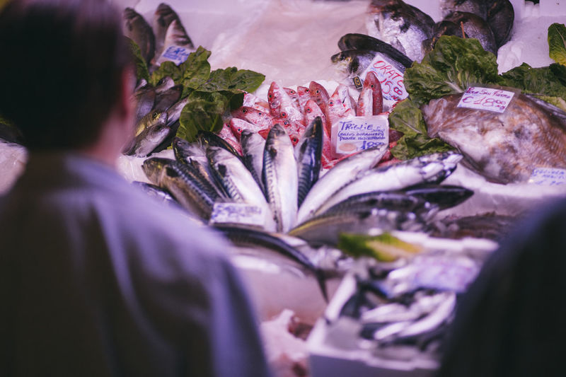 Rear View Of Man Selling Fish At Market Stall