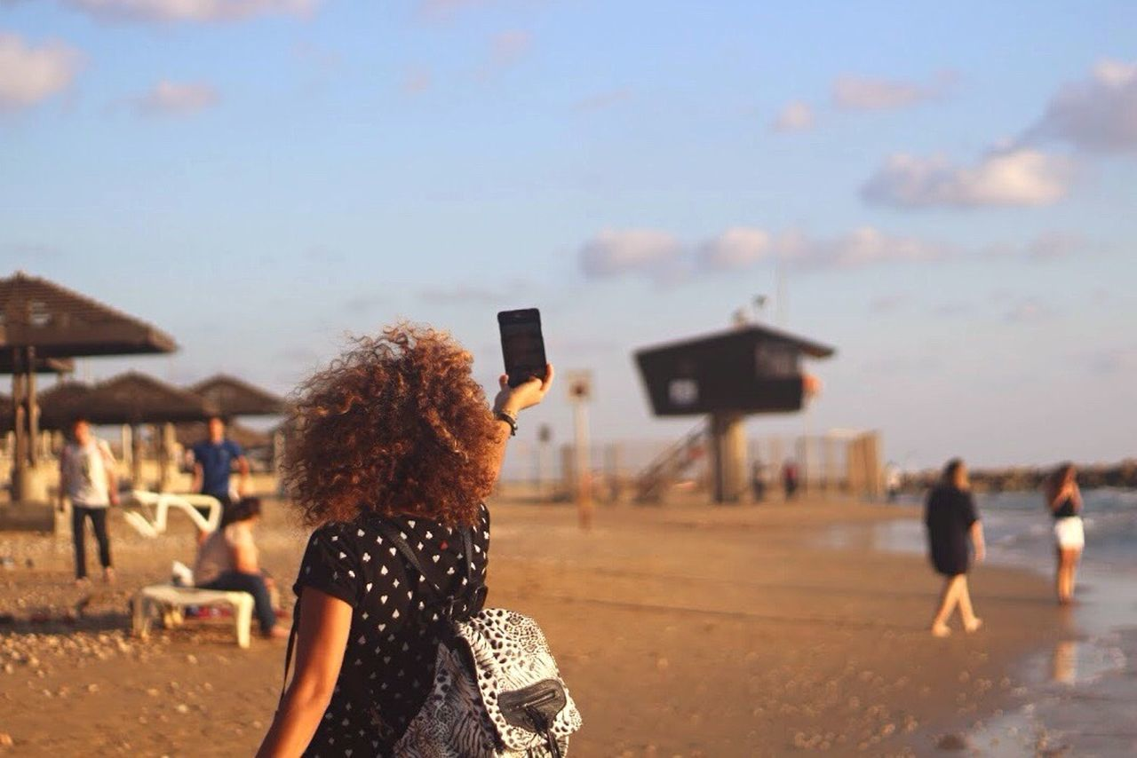 Young woman taking selfie on beach