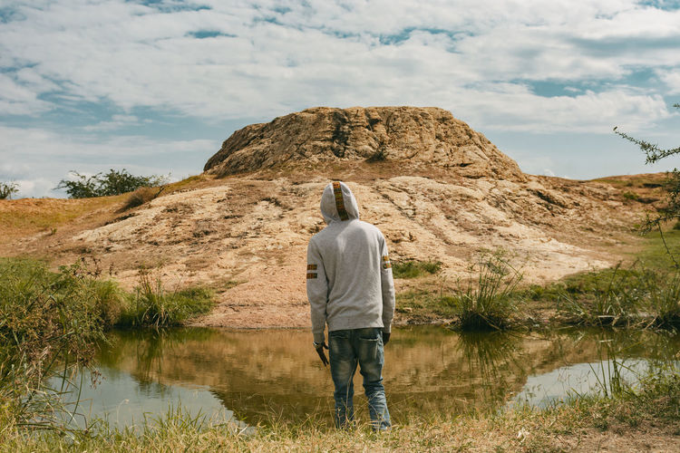 A man standing infront of water looking at a big rock object