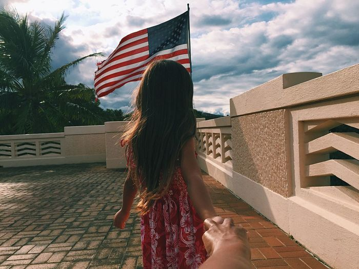 Cropped hand holding girl against american flag at building terrace