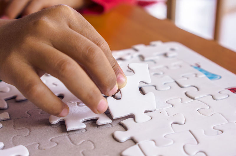 Close-Up Of Hands Playing Jigsaw Puzzle