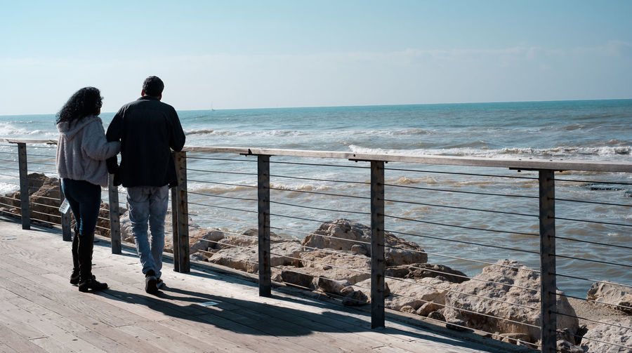 Rear view of people looking at sea against sky