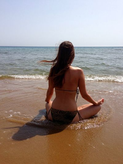 Rear view of woman in bikini meditating while sitting at beach against sky
