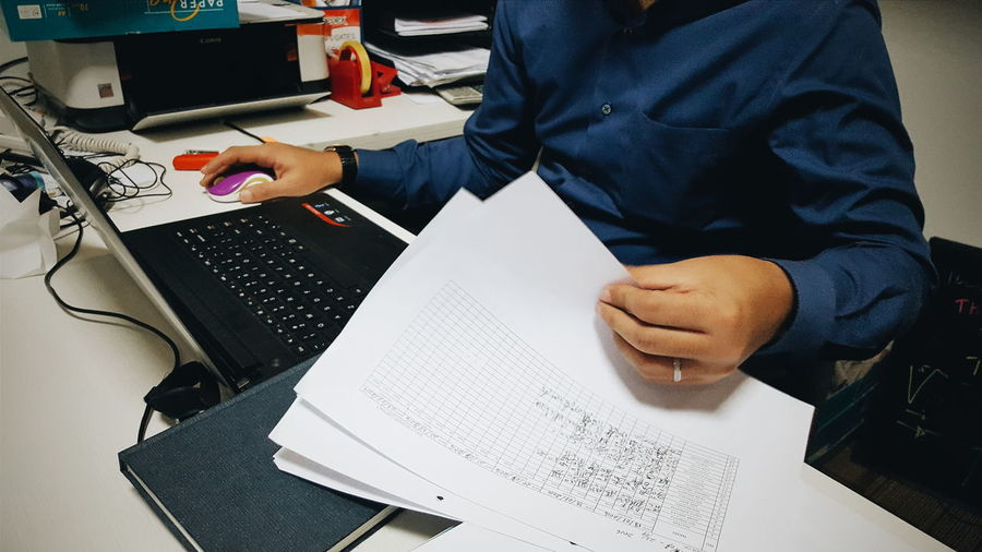 Midsection Of Businessman Working On Laptop With Documents At Desk In Office