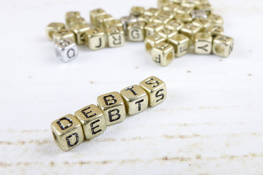 DEBT CONCEPT WITH GOLD DICE ON A WOODEN TABLE Arts Culture And Entertainment Close-up Communication Credit Card Debt Crisis Focus On Foreground Gambling High Angle View Indoors  Large Group Of Objects Leisure Activity Leisure Games Letter No People Number Still Life Studio Shot Table Text Toy Toy Block Western Script