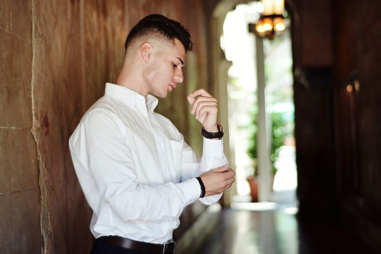 Side view of young man fixing his sleeve