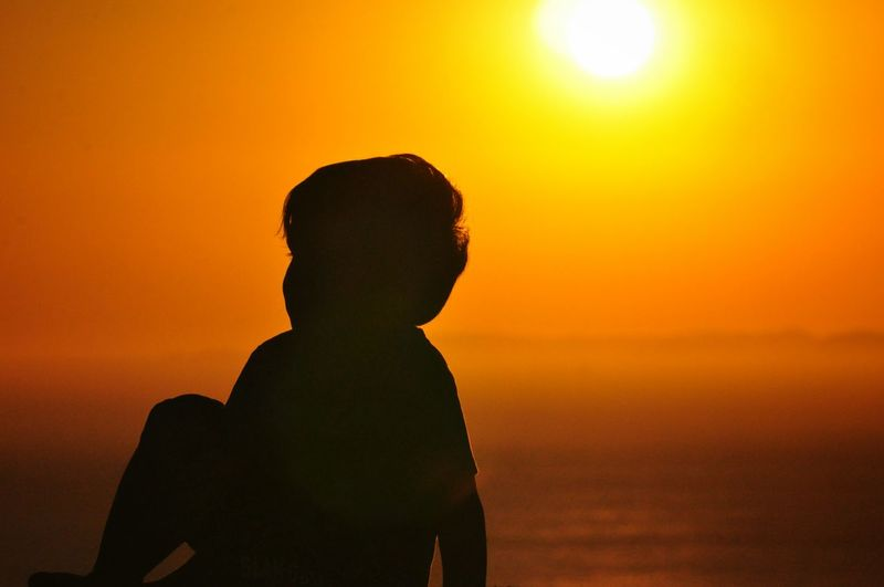 Silhouette Boy Sitting Against Sea During Sunset