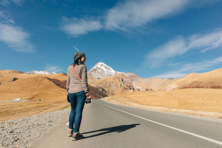 Woman standing on road by mountains against sky