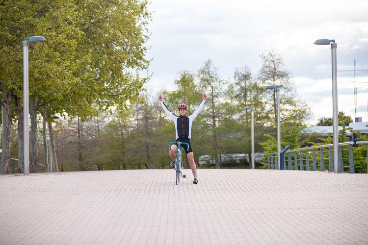 Full length of boy jumping against trees