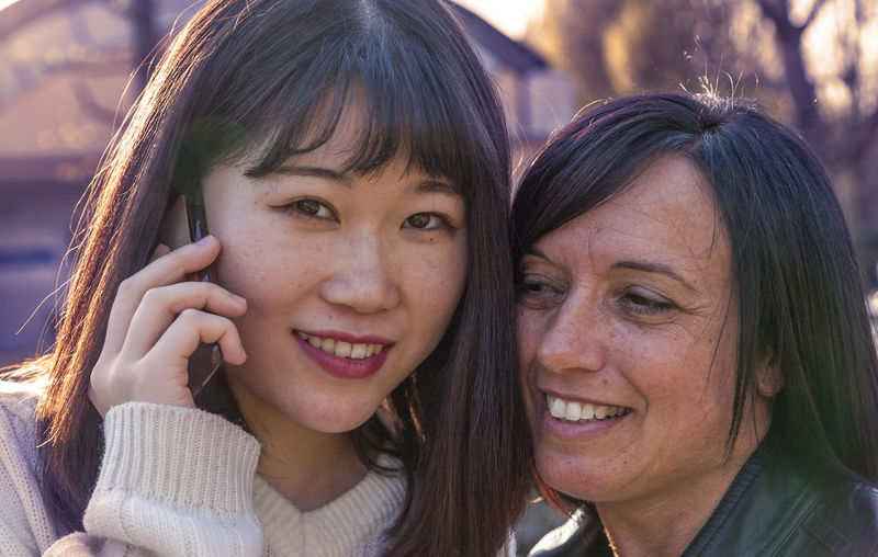 Close-up of colleague talking on phone outdoors