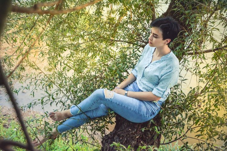 High angle view of woman sitting on branch
