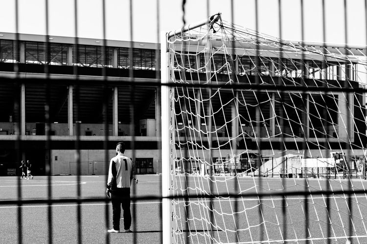 Goalie standing against goal post on field seen from fence