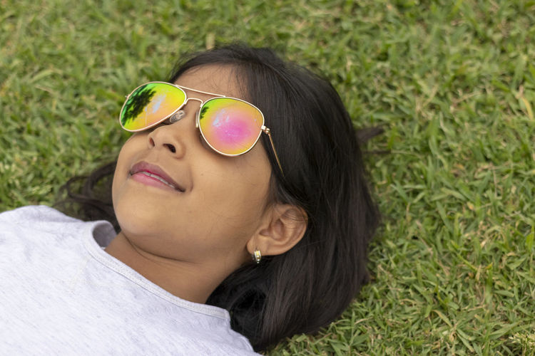 Beautiful girl with sunglasses lying on the grass Glasses Sunglasses Fashion One Person Headshot Portrait Leisure Activity Grass Day Women Hair Real People Lifestyles Females Plant Lying Down Black Hair High Angle View Hairstyle Outdoors Beautiful Woman Teenager