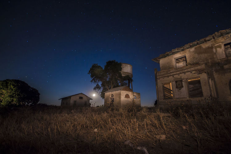 Low angle view of abandoned house on field against sky at night