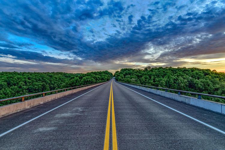 Road leading towards trees against sky
