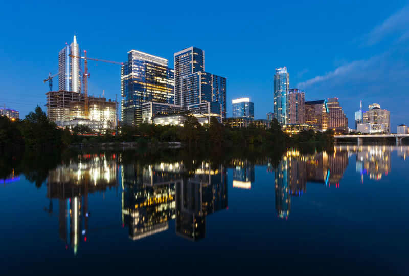 Austin, Texas with new buildings rising, reflecting in lady Bird Lake during sunset / Austin Skyline and new constructions Austin, TX Texas Architecture Blue Building Exterior Built Structure City Cityscape Illuminated Lake Mirroring In Water Modern No People Outdoors Reflecting Pool Reflection Reflexions Sky Skyscraper Symmetry Urban Skyline Water Waterfront An Eye For Travel