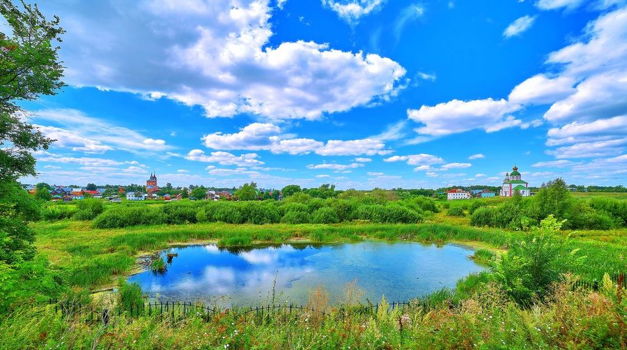 Wide angle sunny landscape of summer Suzdal Russian Culture Countryside Village Horizon Reflection Blue Building Exterior Pond Fences Green Wide Angle Suzdal Sunny Summer Tree Water Agriculture Landscape Cloud - Sky Plant Skyline Waterfront Standing Water