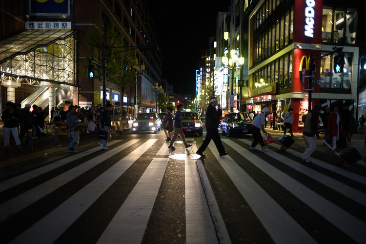 People walking on illuminated street at night