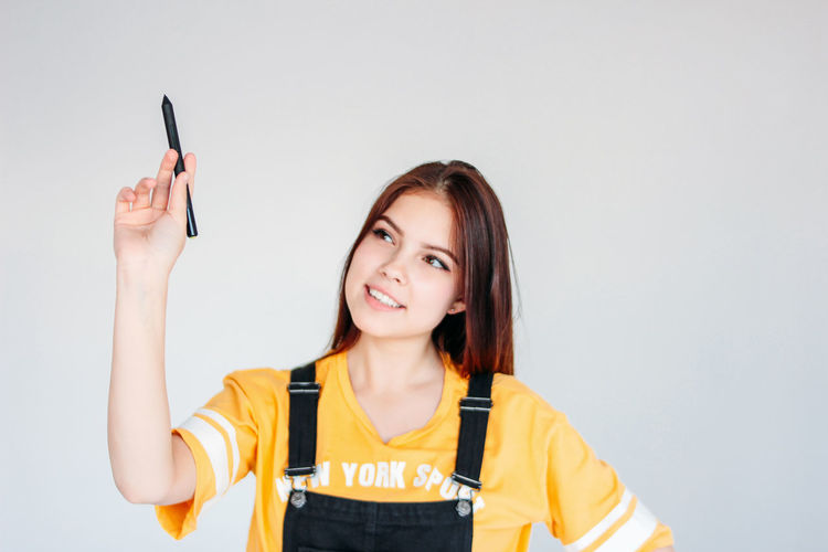 Smiling young woman holding digitized pen against gray background