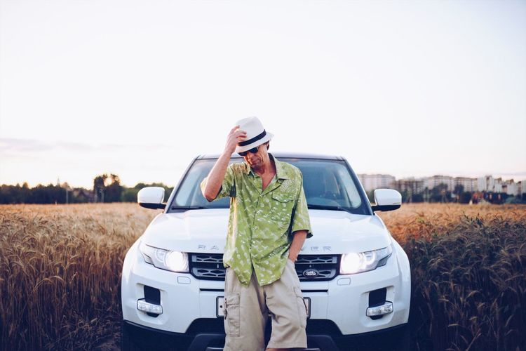 Man holding camera while standing by car on field against sky