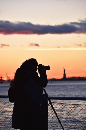 Silhouette woman photographing by sea against sky during sunset