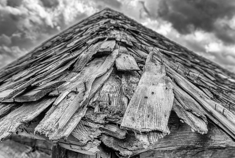Low angle view of wooden structure against cloudy sky