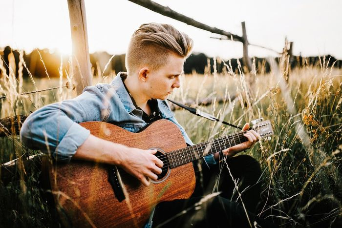 - Dominic Donner - EyeEm Selects Guitar Plucking An Instrument Music Musical Instrument One Person Casual Clothing Playing Leisure Activity Field One Man Only Young Adult Outdoors Adult Sommergefühle Lifestyles Only Men People Grass Portrait Nature Summer Singer  Songwriter EyeEm Best Shots