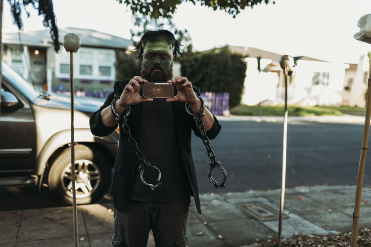 Man photographing with mobile phone while standing on bus