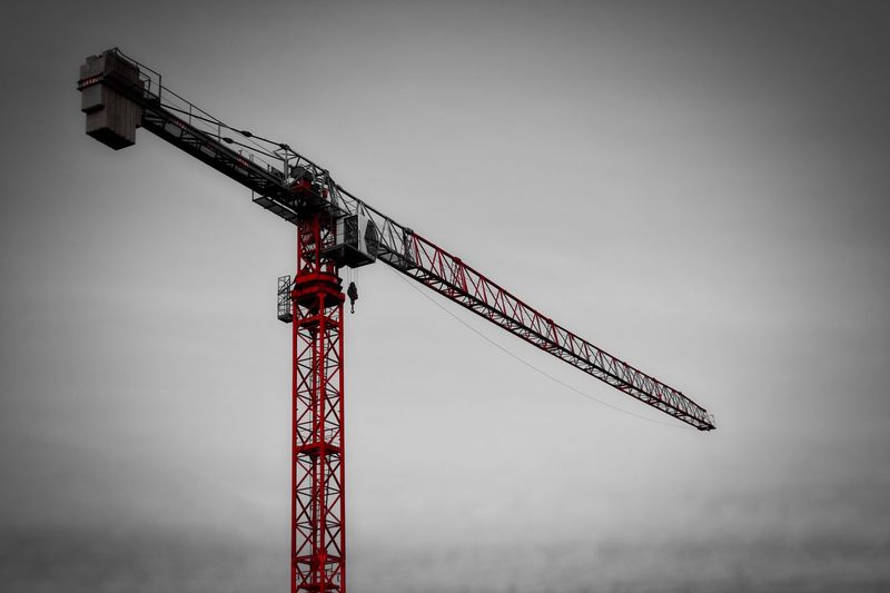 Low angle view of crane at construction site against sky