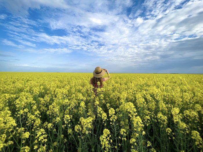 Rear view of woman wearing dress and hat in a field of canola flowers on a cloudy day