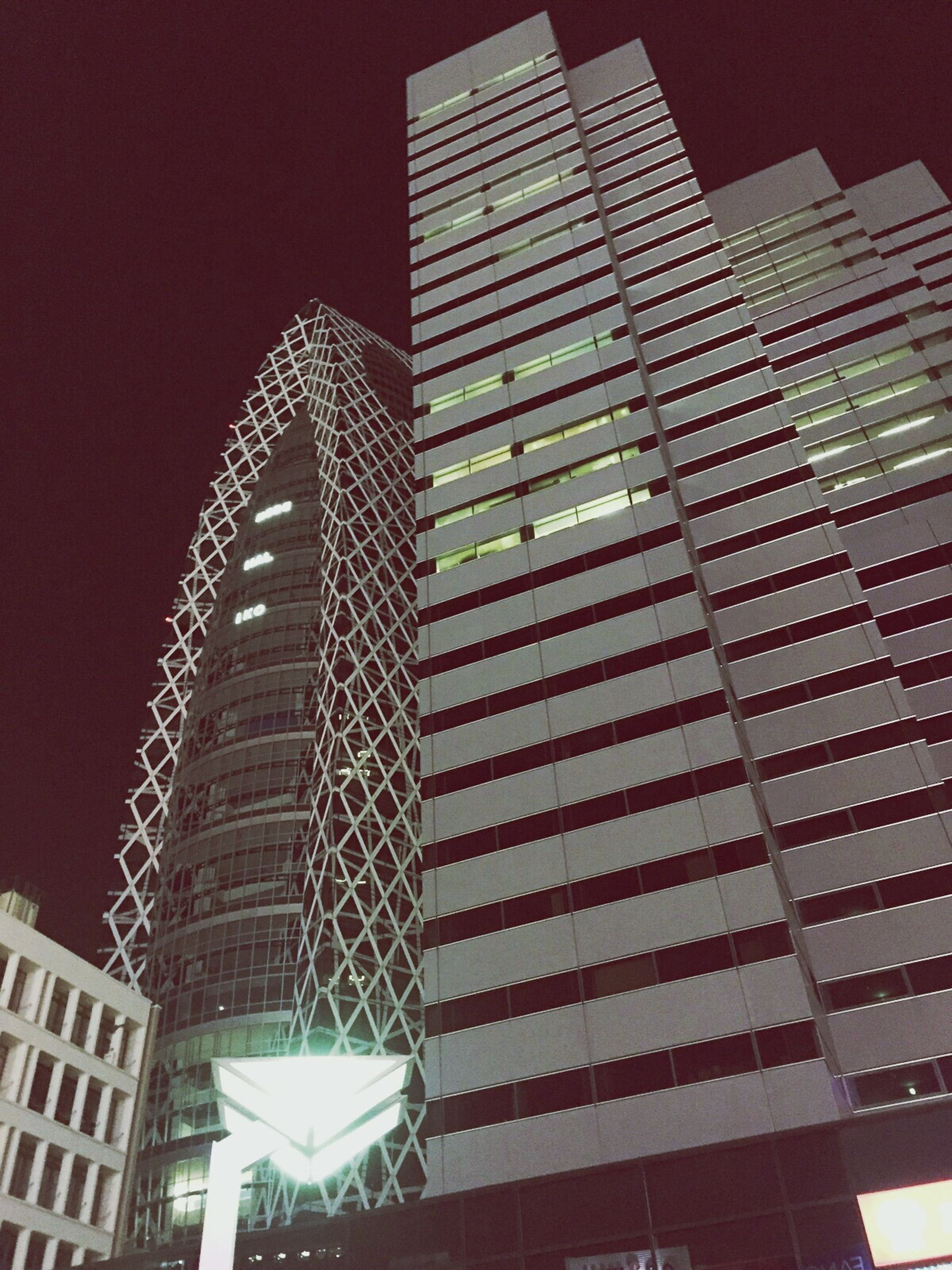 building exterior, architecture, built structure, low angle view, city, modern, skyscraper, night, illuminated, office building, tall - high, building, tower, clear sky, sky, tall, outdoors, city life, no people, pattern